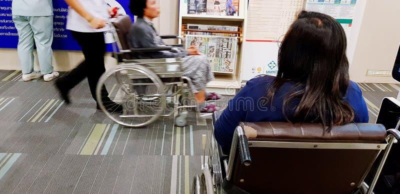Donna asiatica che si siede sulla sedia a rotelle in ospedale e che aspetta per vedere medico immagini stock