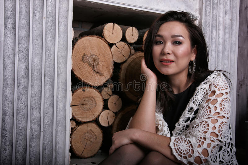 Donna asiatica che si siede vicino al camino con lo scialle sulle sue spalle fotografie stock