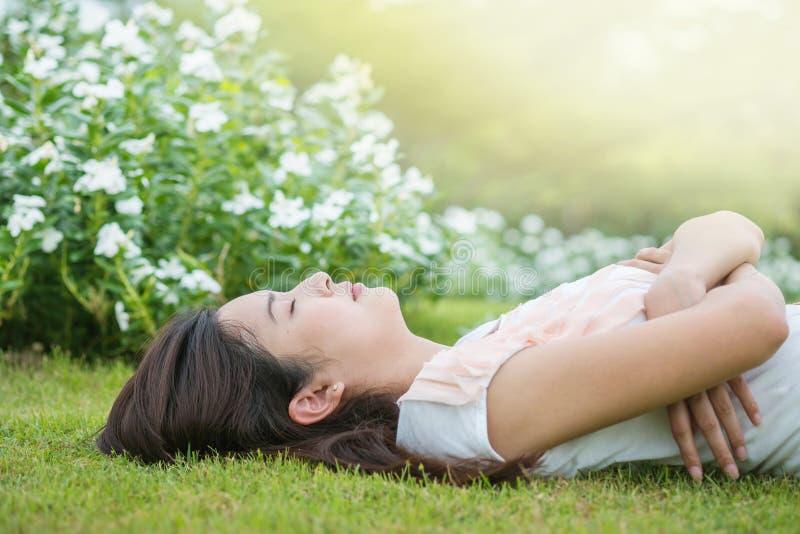 Donna asiatica che si trova e che dorme sul campo di erba dopo che lei stanca nel pomeriggio immagine stock