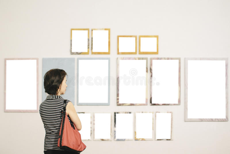 Donna asiatica che sta in una galleria di arte fotografia stock libera da diritti