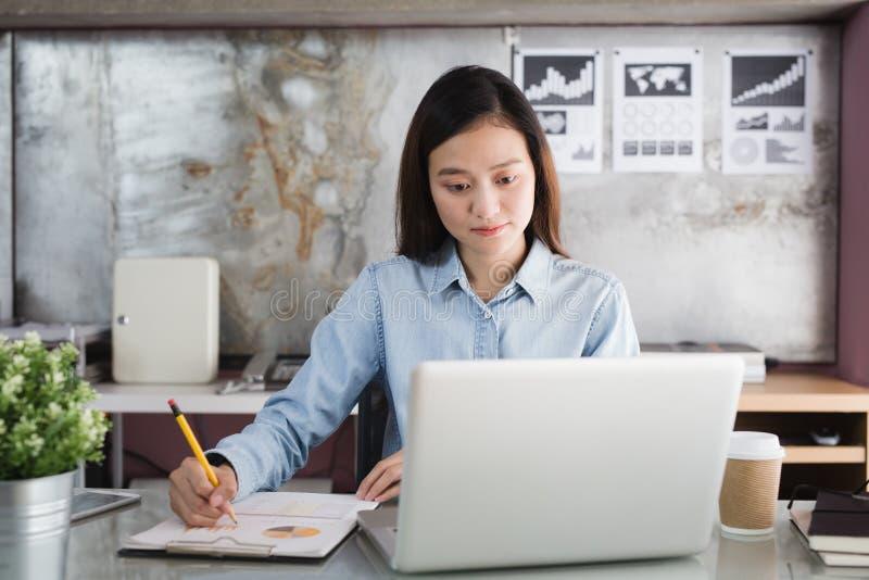Donna asiatica che tiene matita gialla a disposizione e che per mezzo del computer portatile, funzionamento femminile in scrivani fotografie stock