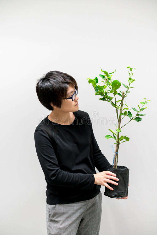 Donna asiatica che tiene pianta verde nella borsa nera della pianta fotografia stock libera da diritti