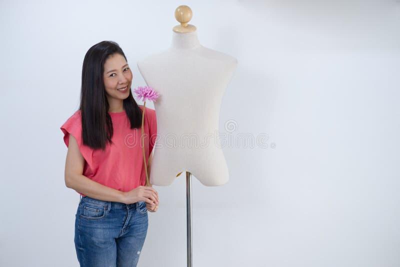 Donna asiatica che tiene un fiore rosa in mani e supporto accanto al maschio mannequin1 immagine stock libera da diritti