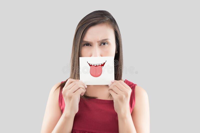 Donna asiatica che tiene una carta con un fronte sveglio della lingua su davanti alla sua bocca immagine stock