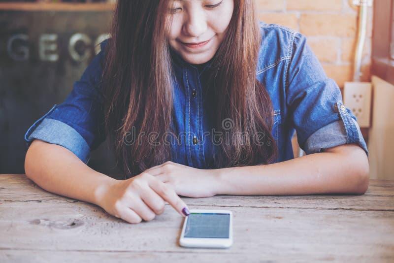 Donna asiatica che tocca e che utilizza Smart Phone con ritenere felice mentre sedendosi nel caffè di legno d'annata immagini stock libere da diritti