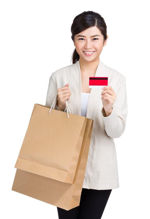 Donna asiatica che usando la carta di credito con il sacchetto della spesa fotografia stock