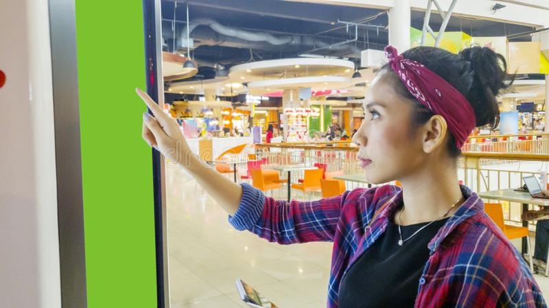 Donna asiatica che utilizza un chiosco self service nel centro commerciale fotografie stock
