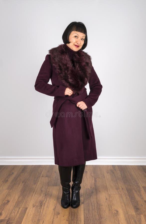 Donna asiatica con brevi capelli neri che portano un cappotto 2 della lana colorato Borgogna fotografia stock