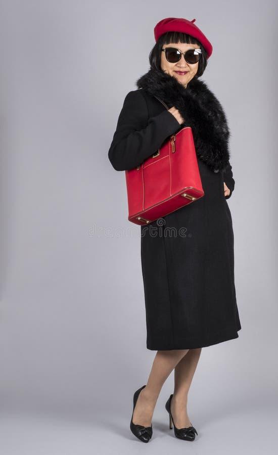 Donna asiatica con i capelli di scarsità che portano un cappello rosso del berretto e un cappotto nero della lana immagine stock libera da diritti