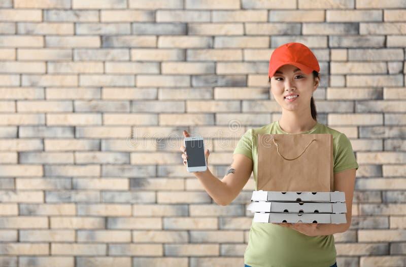 Donna asiatica con i contenitori di pizza del cartone, il sacco di carta ed il telefono cellulare sul fondo del muro di mattoni S immagine stock