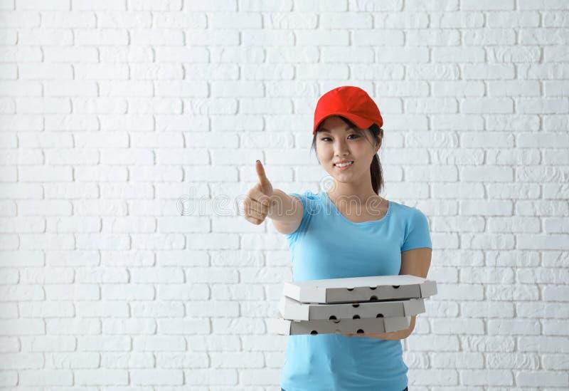 Donna asiatica con i contenitori di pizza del cartone sul fondo del muro di mattoni Servizio di distribuzione dell'alimento immagine stock