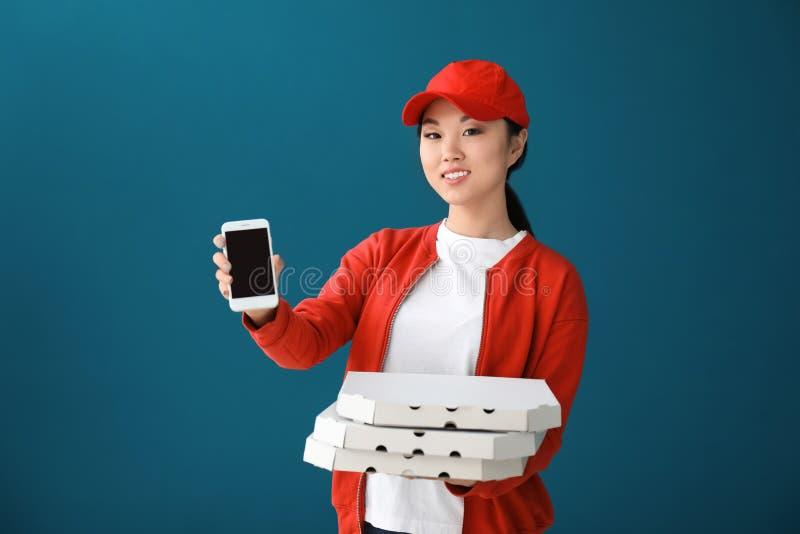 Donna asiatica con i contenitori ed il telefono cellulare di pizza del cartone sul fondo di colore Servizio di distribuzione dell fotografia stock