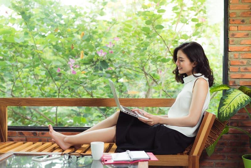 Donna asiatica con il computer portatile che si siede vicino alla finestra in ufficio creativo o fotografie stock