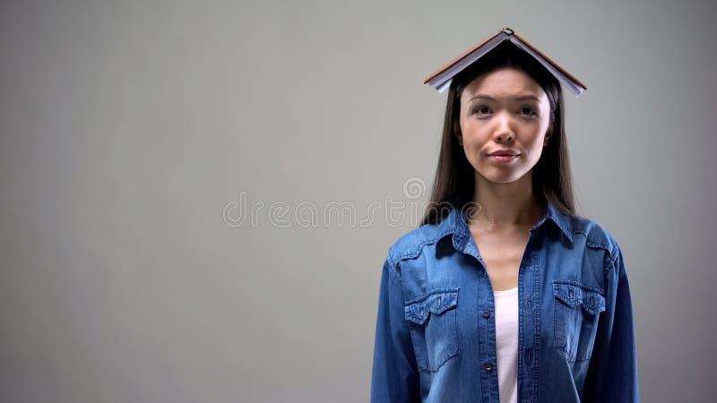 Donna asiatica con il libro sulla condizione capa sul fondo grigio, studente universitario fotografia stock libera da diritti