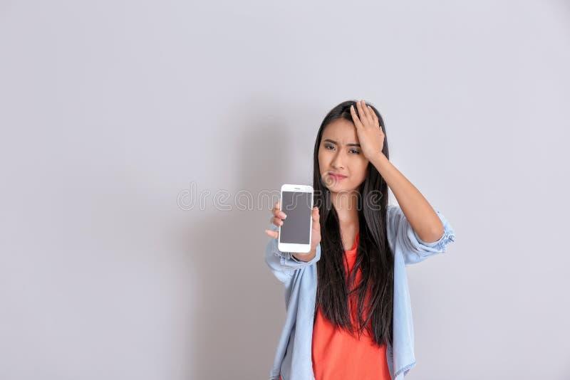 Donna asiatica con il telefono cellulare inoperante su fondo bianco fotografia stock libera da diritti