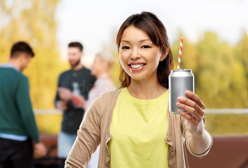 Donna asiatica con la bevanda della latta sopra il partito del tetto immagine stock