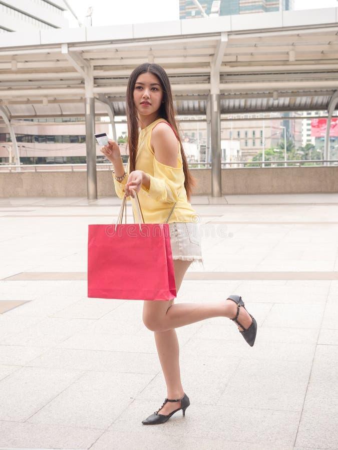 Donna asiatica con la carta di credito ed il sacchetto della spesa fotografia stock