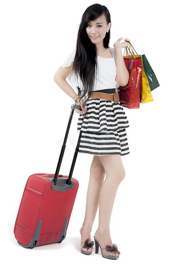 Donna asiatica con la valigia ed i sacchetti della spesa fotografia stock libera da diritti