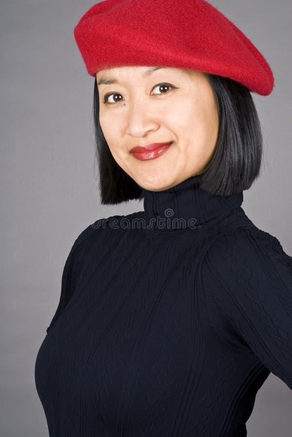 Donna asiatica con un berreto rosso fotografie stock libere da diritti