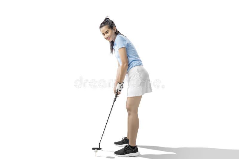 Donna asiatica con un club di golf del putter pronto a colpire la palla fotografia stock libera da diritti