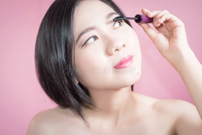 Donna asiatica dei capelli lunghi giovane bella che applica mascara isolata sopra fondo rosa trucco naturale, terapia della STAZI immagine stock