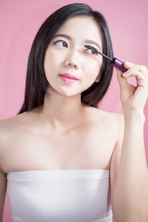 Donna asiatica dei capelli lunghi giovane bella che applica mascara isolata sopra fondo rosa trucco naturale, terapia della STAZI fotografia stock
