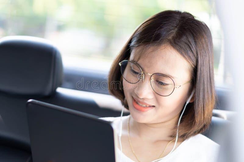 Donna asiatica del primo piano che utilizza compressa digitale in un'automobile con il fronte felice fotografie stock