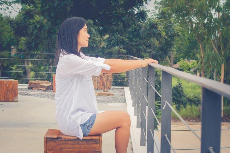 Donna asiatica del ritratto che si siede sulla sedia di legno alla cima piana delle costruzioni del tetto, rilassantesi e sorride immagine stock