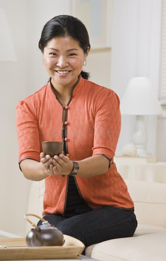 donna asiatica del tè del servizio immagine stock