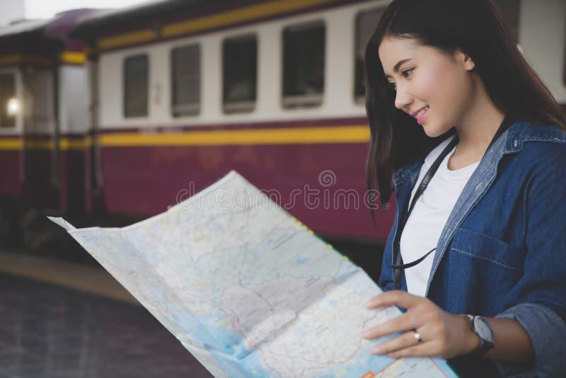 Donna asiatica del viaggiatore che esamina mappa il destinati del ritrovamento della stazione ferroviaria immagini stock libere da diritti