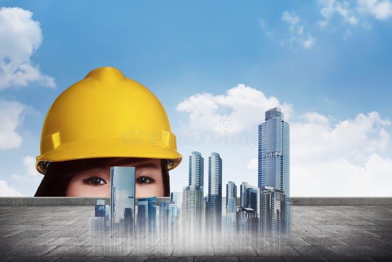 Donna asiatica dell'ingegnere che dà una occhiata dai piani virtuali di costruzione immagine stock