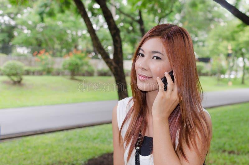Donna asiatica della giovane testarossa attraente sul suo telefono cellulare fotografie stock