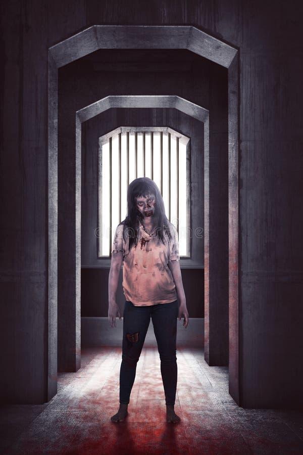 Donna asiatica dello zombie terrificante che sta sul pavimento sanguinoso fotografia stock