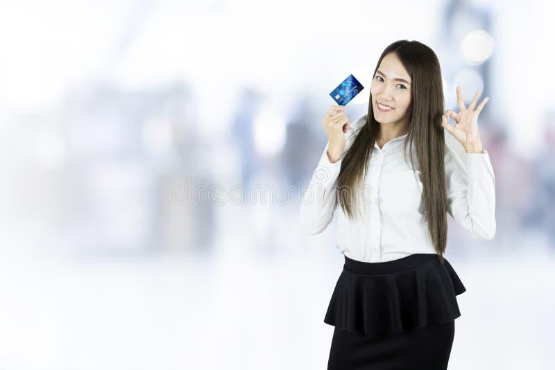 Donna asiatica di affari che mostra la carta di credito fotografia stock