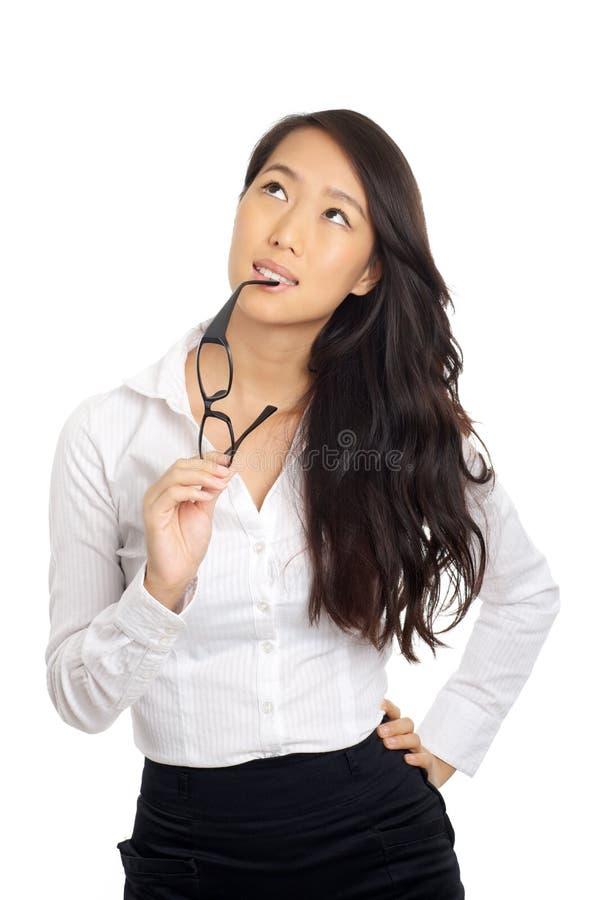 Donna asiatica di affari che pensa con i vetri immagini stock