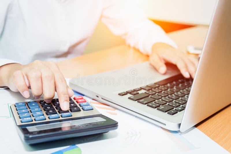 Donna asiatica di affari che per mezzo di un calcolatore per calcolare immagine stock
