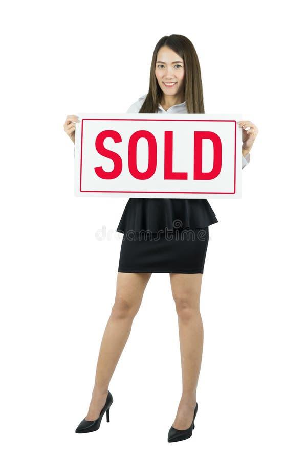 Donna asiatica di affari che sorride e che tiene segno venduto Bella giovane donna caucasica immagini stock