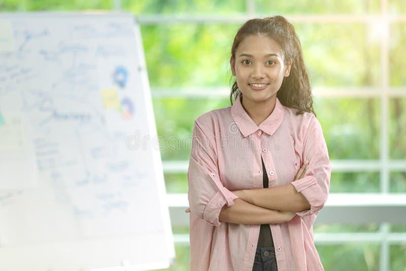 Donna asiatica di affari che sta con lo sguardo sicuro di sé direttamente fotografia stock
