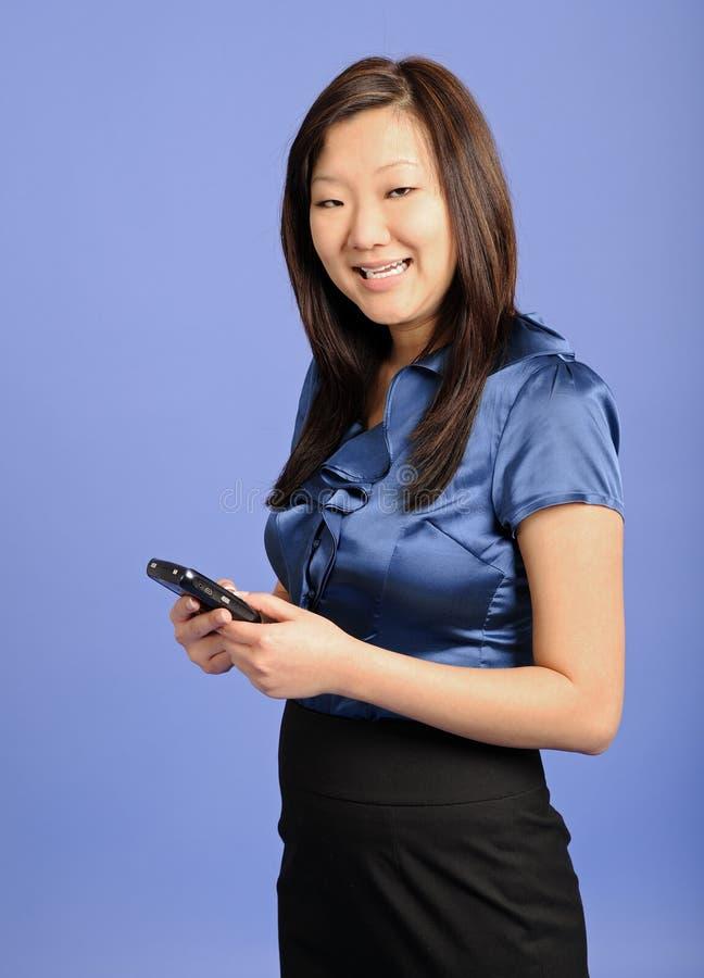 Donna asiatica di affari che usando un PDA fotografia stock