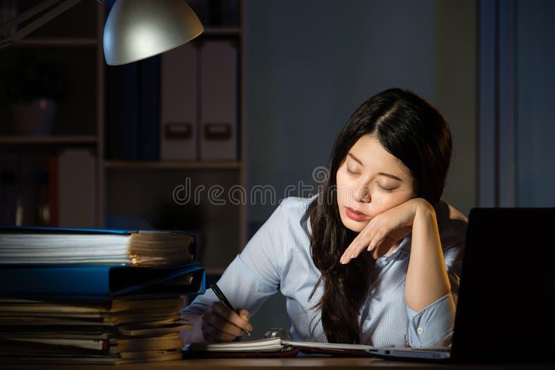 Donna asiatica di affari sonnolenta lavorando fuori orario a tarda notte immagine stock