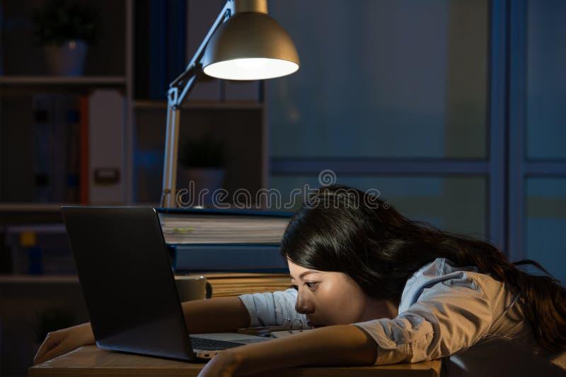 Donna asiatica di affari sonnolenta lavorando fuori orario a tarda notte fotografie stock libere da diritti