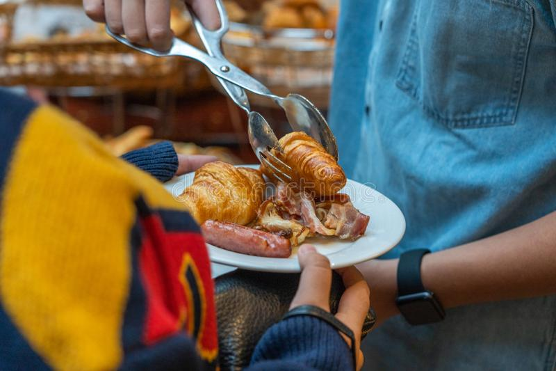 Donna asiatica di aiuto dell'uomo che seleziona croissant gonfio nel suo piatto immagine stock
