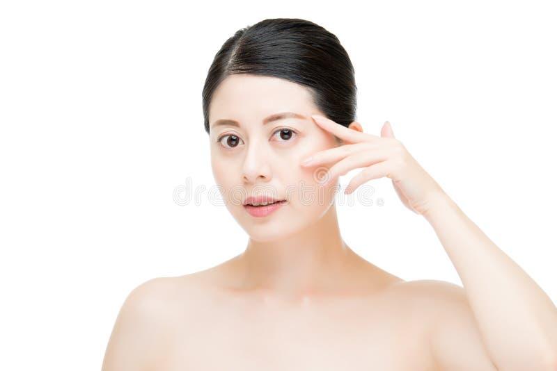Donna asiatica di bellezza che applica gesto di mano crema dell'occhio fotografia stock libera da diritti