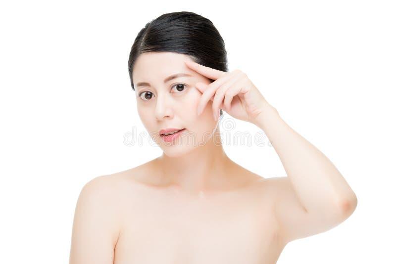 Donna asiatica di bellezza che applica gesto di mano crema dell'occhio immagini stock