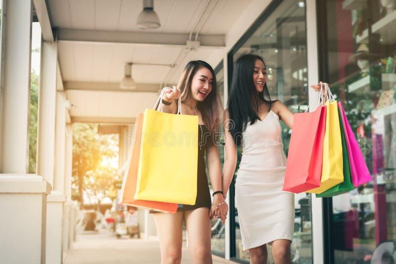 Donna asiatica di bellezza che cammina al centro commerciale e allo shoppi della tenuta immagini stock libere da diritti