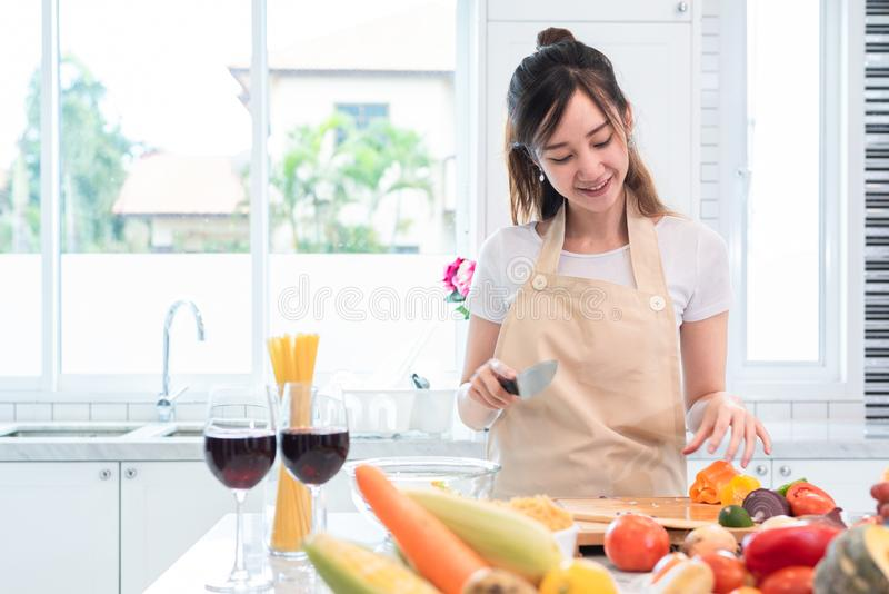 Donna asiatica di bellezza che cucina e che affetta verdura nella stanza della cucina fotografia stock libera da diritti
