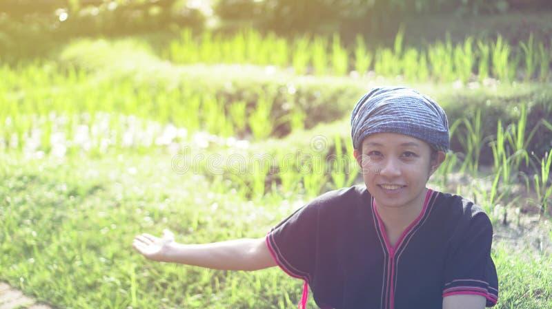 Donna asiatica di etica con il sorriso indigeno del vestito al suo riso organico fi fotografia stock libera da diritti