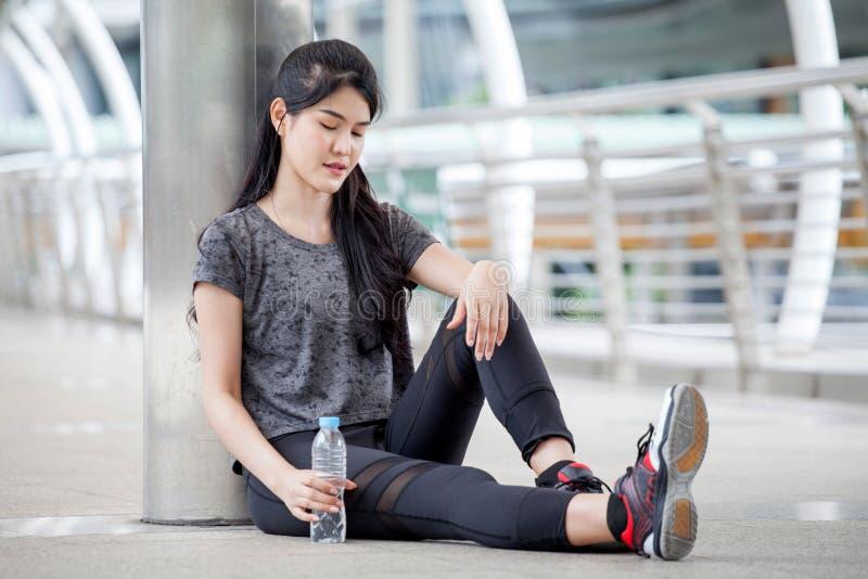 donna asiatica di forma fisica che prende una rottura dopo l'allenamento che si esercita con una bottiglia di acqua sulla via in  immagine stock libera da diritti