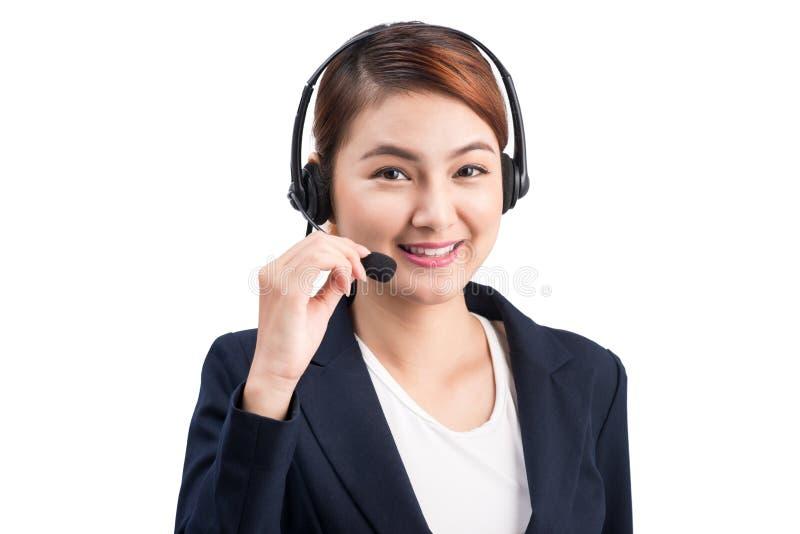 Donna asiatica di giovani affari attraenti che per mezzo di una cuffia avricolare del telefono immagini stock libere da diritti
