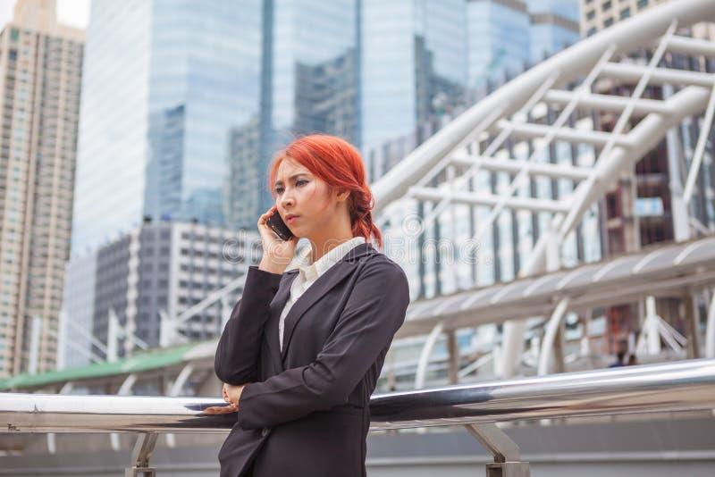 Donna asiatica di giovani affari che rivolge al telefono fotografie stock